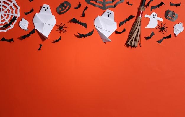 Decoração de papel artesanal de halloween em fundo laranja. fundo de dia das bruxas. copie o espaço