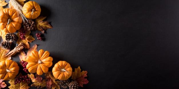 Decoração de parede de ação de graças com folhas secas e abóbora na parede do quadro-negro