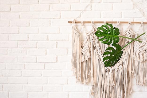 Decoração de parede macramê em estilo boho com duas folhas de monstera em uma parede de tijolos brancos com espaço de cópia.