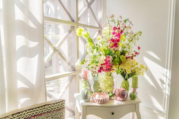 Decoração de páscoa beatuful composição com velas. ovos, coelho, maçãs e flores desabrochando.