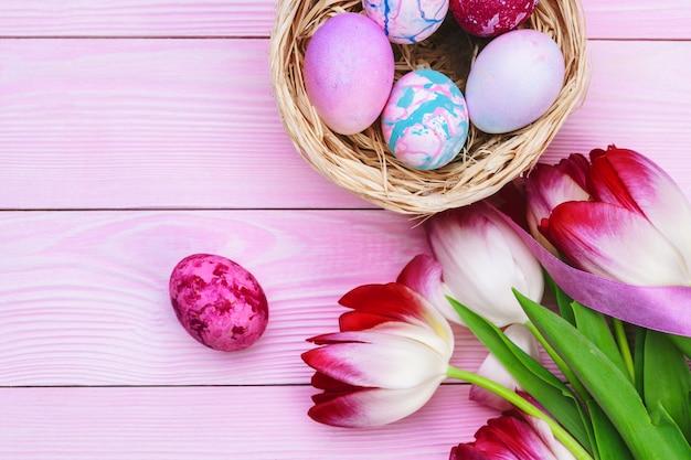 Decoração de páscoa com ovos coloridos e tulipas sobre madeira rosa. vista superior com espaço de cópia