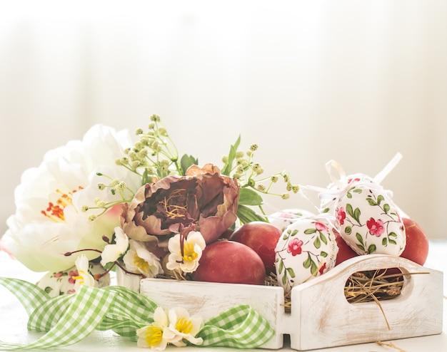 Decoração de páscoa com uma cesta e ovos vermelhos com flores