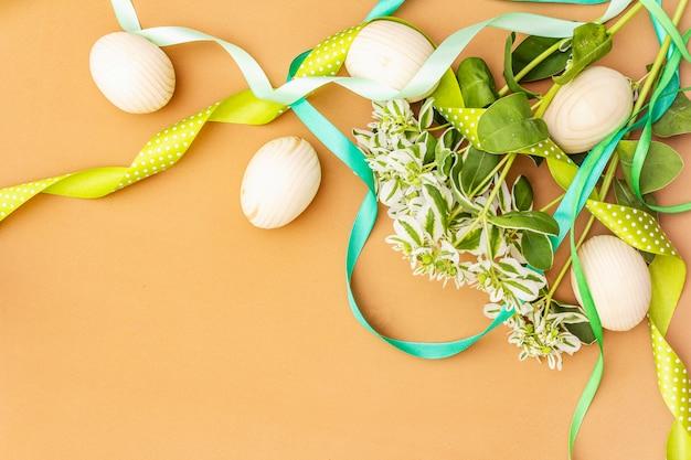 Decoração de páscoa ovos, fitas, flores frescas e folhas.