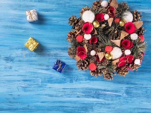 Decoração de porta de natal com pequenas caixas de presente sobre fundo azul de madeira. símbolo de saudação.