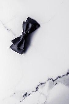 Decoração de presente de feriado e conceito de promoção de venda fita de seda preta e arco em fundo de mármore f ...