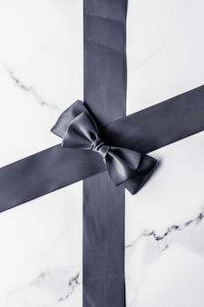 Decoração de presente de feriado e conceito de promoção de venda fita de seda preta e arco em plano de fundo de mármore