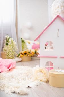 Decoração de primavera com flores e grande casa de bonecas.