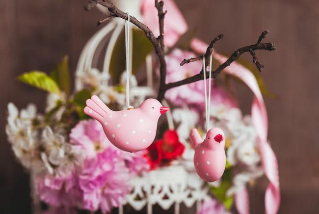 Decoração de primavera - pássaros rosa no galho em uma gaiola chique com flores