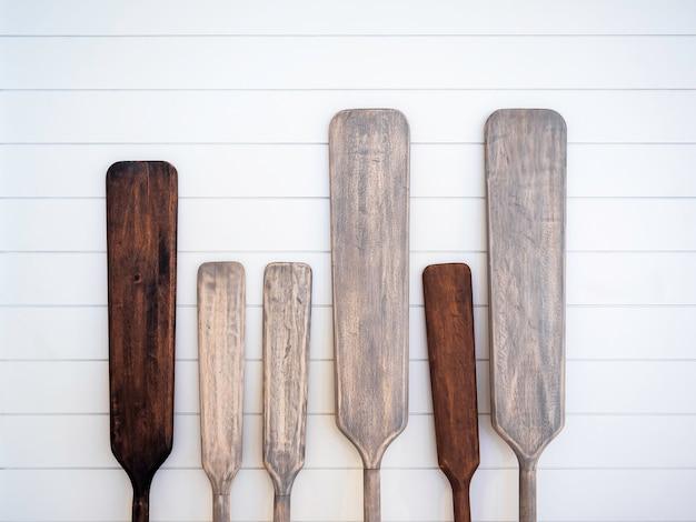 Decoração de remos de canoa de madeira velha na parede de prancha de madeira branca. uma variedade de tamanhos e cores de lâminas e cabos de remos de canoa de madeira.
