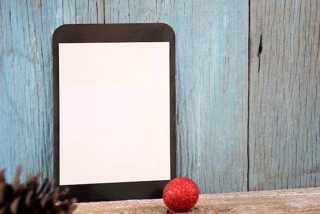 Decoração de tablet e bola de natal em fundo de madeira