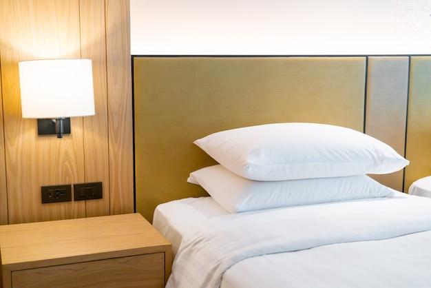 Decoração de travesseiro branco na cama no quarto do hotel