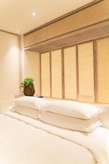 Decoração de travesseiros brancos na cama em quarto de hotel resort de luxo