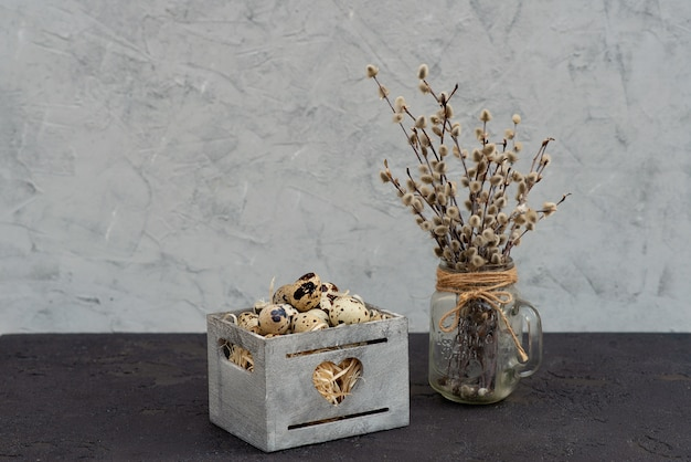 Decoração de um ovo de codorna em uma cesta de madeira com galhos frescos de salgueiro de serapilheira.