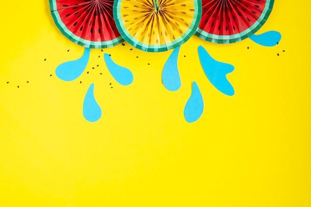 Decoração de ventilador de melancia de origami de frutas de papel. banner criativo com espaço de cópia em fundo amarelo brilhante. verão trópico.