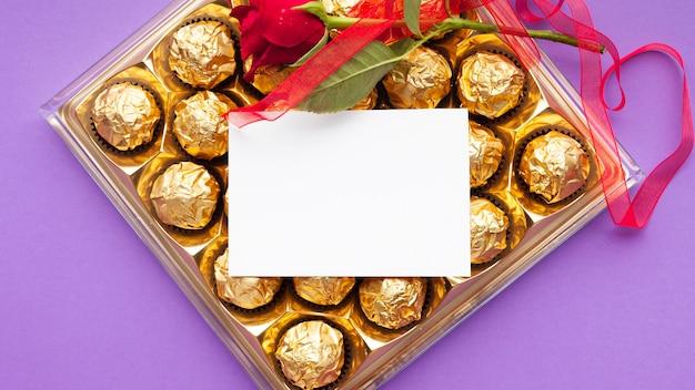 Decoração de vista superior com caixa de chocolate e cartão
