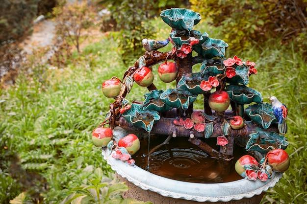 Decoração decorativa do jardim. pote de cerâmica com uma estátua de uma macieira com maçãs vermelhas e um pequeno pássaro multicolorido