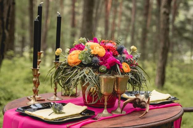 Decoração. detalhes. buque de noiva. composição. decorações de casamento. na mesa de madeira no bosque há um arranjo de flores com flores vermelhas, amarelas, rosa e verdes, velas, estatuetas.