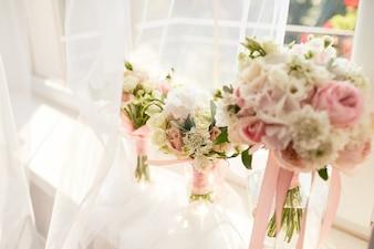 Decoração do casamento. Buquê de rosa cor de rosa brilhante para uma noiva e damas de honra diante de uma janela