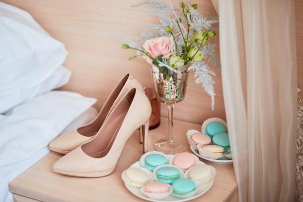 Decoração do casamento. sapatos da noiva bege, buquê e placa com macaroons estão na mesa
