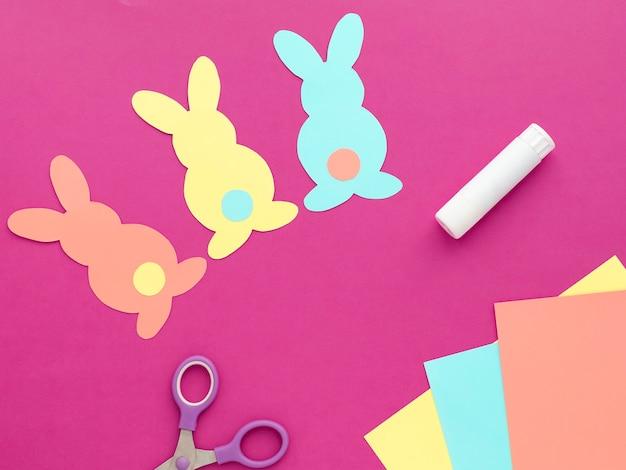 Decoração do coelhinho da páscoa. corte de papel coelhos coloridos de férias diy. vista superior, copie o espaço no fundo rosa.