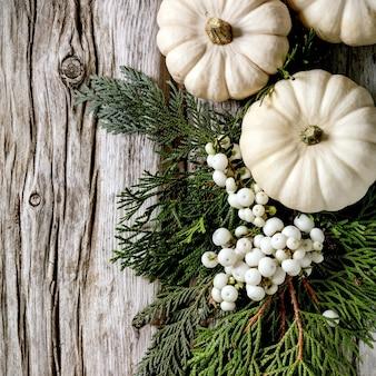 Decoração do feriado com abóboras decorativas brancas, abóboras de argila artesanais, ramos de thuja, bagas sobre fundo de madeira velho. postura plana, copie o espaço. imagem quadrada