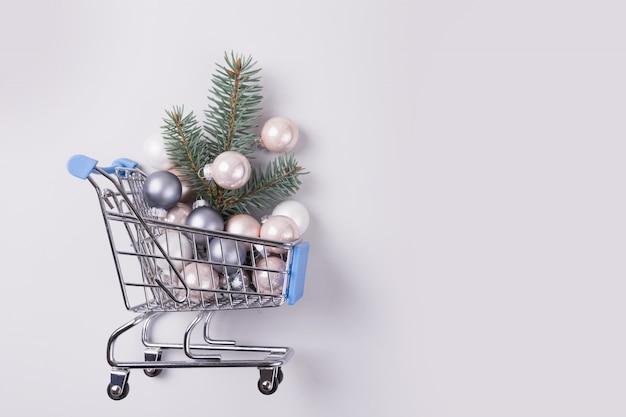 Decoração do natal no conceito do carrinho de compras - trole o carrinho completamente das bolas e da árvore do xmas. dia de boxe. vista do topo.