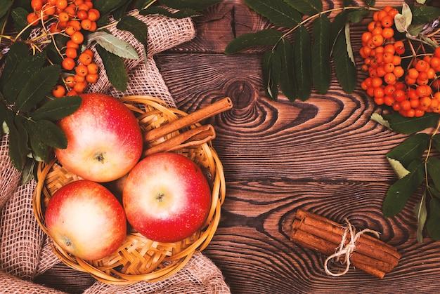 Decoração do outono com maçãs, canela e um ramo de rowan em uma mesa de madeira.