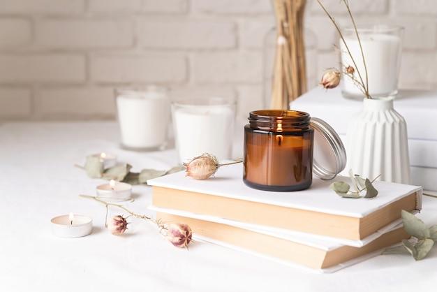Decoração e interiores da casa. lindas velas acesas com folhas de eucalipto e flores secas em uma pilha de livros brancos