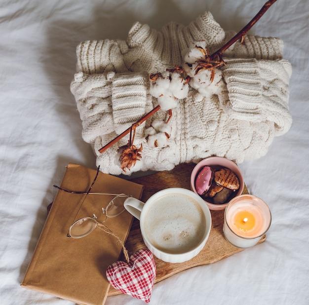Decoração ecológica para a casa. decoração aconchegante em casa. uma caneca de cappuccino, biscoitos, uma vela na cama. manhã de inverno. feriados.