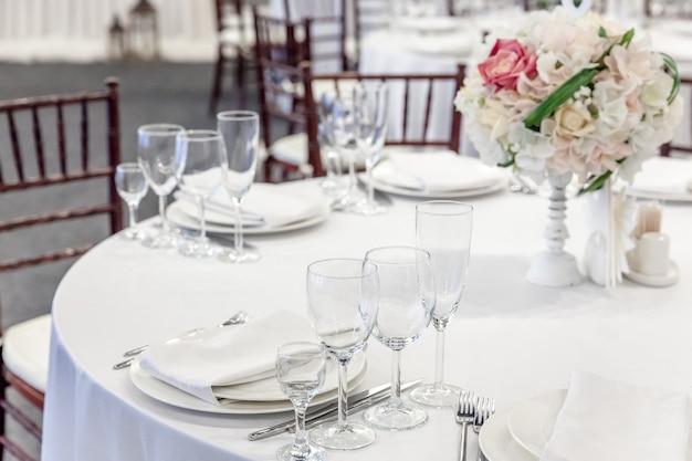 Decoração elegante de banquete de casamento e itens para comida dispostos na mesa branca