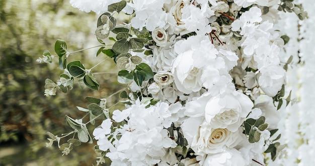 Decoração em arco com flores brancas para cerimônia de casamento na natureza