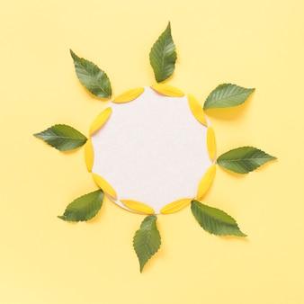 Decoração em forma de girassol composta de folhas; pétalas e papel cartão em branco