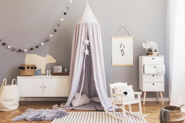 Decoração escandinava elegante e brilhante do quarto do bebê recém-nascido com mock up de pôster, móveis de design branco, brinquedos naturais, dossel cinza pendurado com berço de madeira, estante de livros, acessórios e ursinhos de pelúcia.
