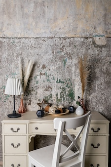 Decoração escandinava para aconchegante casa feita com ervas secas, lâmpada, velas e guirlandas na parede de concreto. flores secas e vegetação em um interior moderno. decoração de interiores em estilo ecológico