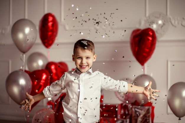 Decoração festiva para um aniversário ou dia dos namorados. balões em forma de grandes corações vermelhos e confetes. menino alegre criança sopra e lança confete
