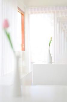 Decoração floral interior para casa. composição branca suave floral mínima em um vaso no fundo da parede branca. Foto Premium