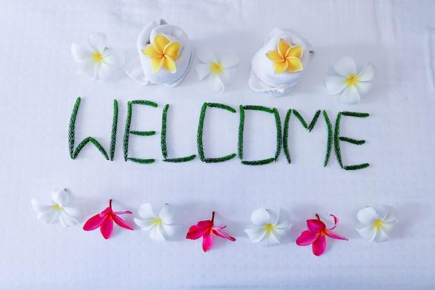 Decoração floral, toalha floral e palavra bem-vindo na cama no quarto de hotel