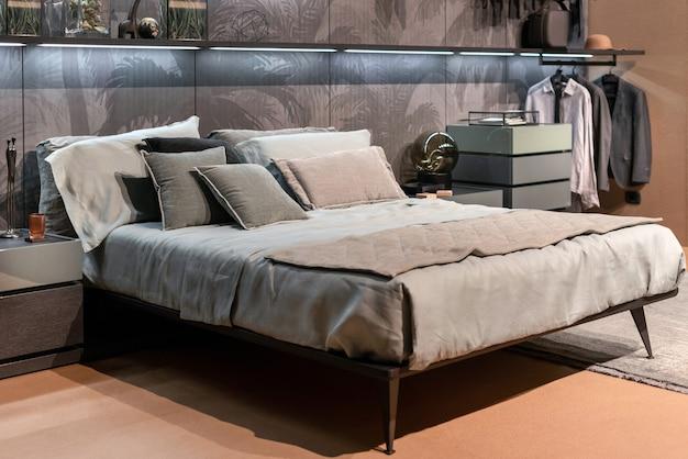 Decoração interior de um quarto de luxo minimalista monocromático com cama de casal em estilo divã, ternos pendurados em um rack e palmeiras tropicais visíveis atrás de uma tela