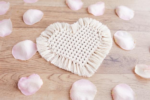 Decoração macramê. dia de são valentim. coração e pétalas de rosa. materiais naturais, fios de algodão. decorações ecológicas, enfeites, decoração feita à mão em mesa de madeira
