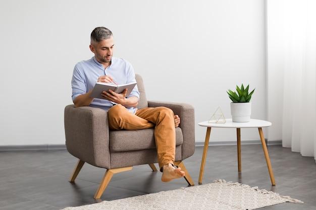 Decoração minimalista e homem sentado em uma cadeira com sua agenda
