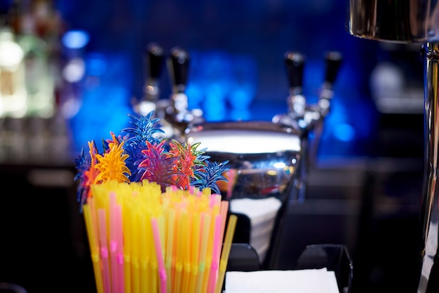 Decoração multicolorida para cocktails em forma de folhas close-up em um fundo escuro turva.