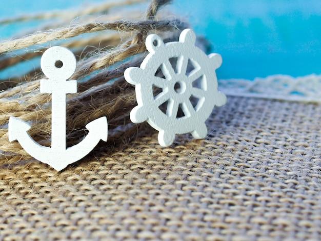 Decoração náutica com um leme e uma âncora, em uma textura branca, superfície, espaço, viagens, férias