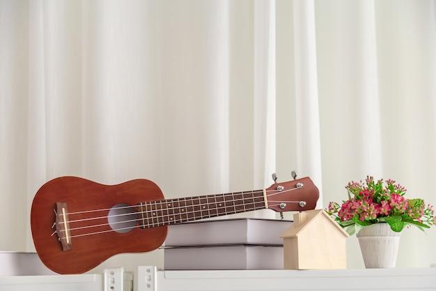 Decoração no quarto com mini guitarra e livro com flor.