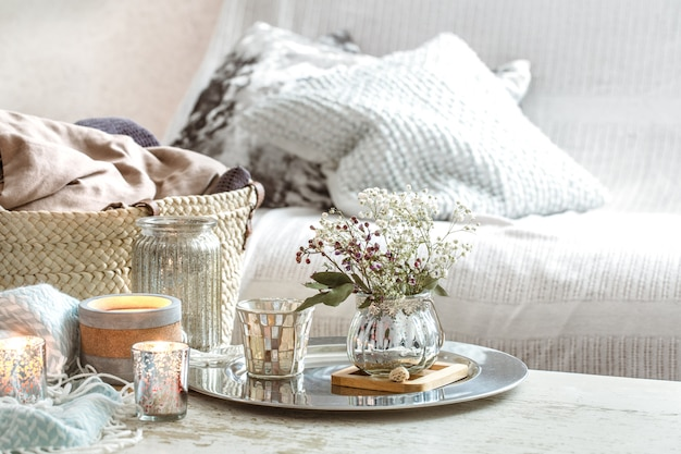 Decoração para casa no interior. um cobertor turquesa e cesta de vime com um vaso de flores e velas