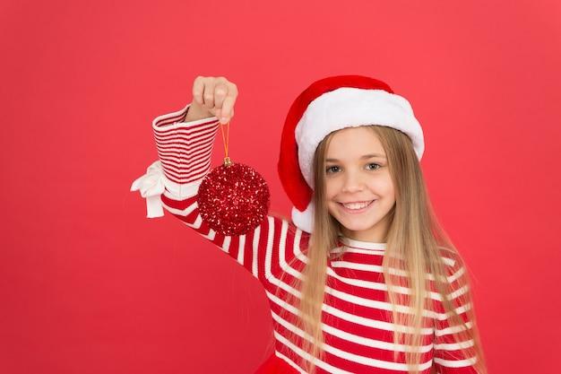 Decoração para trazer alegria do feriado para você. criança feliz segura decoração de bola vermelha brilhante. ornamento e decoração de bola. decoração de férias. decoração de natal favorita. melhor maneira de decorar a árvore de natal.