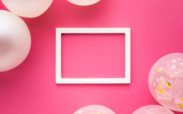 Decoração plana leiga com balões, moldura e fundo rosa