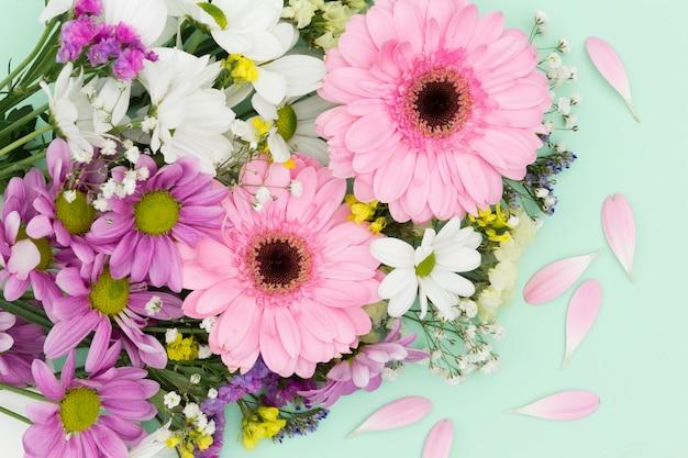 Decoração plana leiga com flores sobre fundo verde