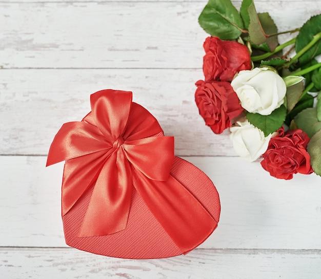 Decoração romântica de dia dos namorados com rosas vermelhas e caixa de presente. feliz dia dos namorados cartão.