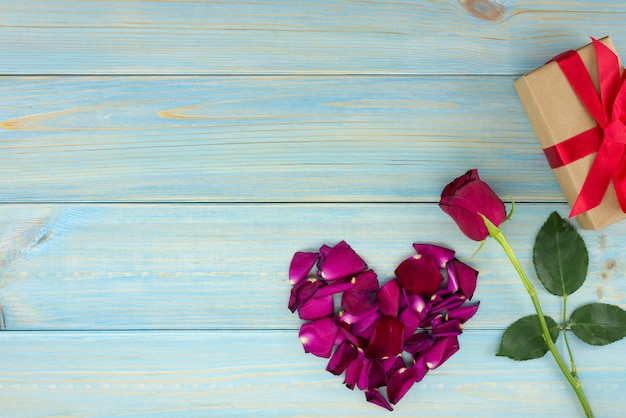 Decoração romântica do dia de valentim com rosas e caixa do gif em uma tabela de madeira azul.