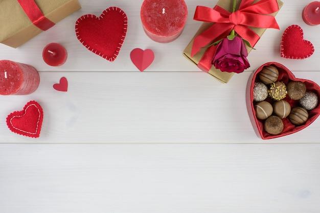 Decoração romântica do dia de valentim com rosas e chocolate em uma tabela de madeira branca.